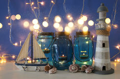 Magical mason jars whith candle light and wooden boat on the shelf. Nautical concept Royalty Free Stock Photography
