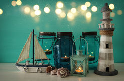 Magical mason jars whith candle light and wooden boat on the shelf. Nautical concept Royalty Free Stock Image