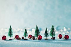 Magical miniature winter wonderland background. Evergreen trees, pine cones and red christmas baubles on shiny blue background. Magical miniature winter royalty free stock photos