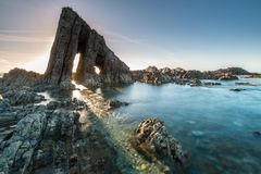 Magical monolith in Asturian beach. Called the Esquiton, where the sun is filtered in summer Royalty Free Stock Image