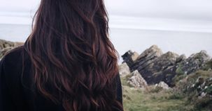 Magical and mystic girl looking to the coast from a cliff in Ireland. 4k stock video footage