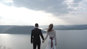 Magical and mystical couple looks at the coast from a cliff. stock footage