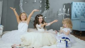 Magical new year, kids in white dresses with artificial snow at studio on winter photoshoot with pet. Magical new year, kids in white dresses with artificial stock footage