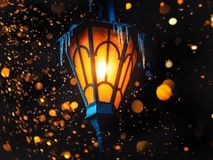 A Magical Old Street Lantern Shines on the Street at Night. Many bright lights around.. Vintage Old Street Classic Iron Lantern On. The House Wall. Christmas or stock photo