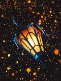 A Magical Old Street Lantern Shines on the Street at Night. Many bright lights around.. Vintage Old Street Classic Iron Lantern On. The House Wall. Christmas or royalty free stock photo