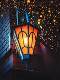 A Magical Old Street Lantern Shines on the Street at Night. Many bright lights around.. Vintage Old Street Classic Iron Lantern On. The House Wall. Christmas or royalty free stock photos