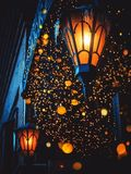 A Magical Old Street Lanterns Shines on the Street at Night. Many bright lights around. Vintage Old Street Classic Iron Lanterns O. N The House Wall. Christmas royalty free stock photography