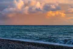 Magical pale pink sky. With fluffy colorful clouds at sunset and the sea Stock Photo