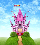 Magical Pink Castle. As a fantasy princess with a fun royal kingdom on a green grass mountain top with a golden path as a girls toy dream or dreaming of a fairy Stock Photo