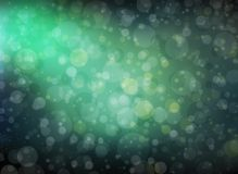 Pretty bokeh background with sunbeam or rays shining through round circle shapes floating in bright blue green sky Stock Photos