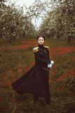 Magical pretty girl with sword stands in a field of flowers. The wind ruffles coat Royalty Free Stock Images