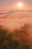 Magical red daybreak. Misty daybreak in a beautiful hills. Peaks of hills are sticking out from foggy background, the fog is red. Red daybreak. Misty daybreak in Royalty Free Stock Photo