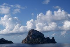 Magical Rock Es Vedra Ibiza. The second most energetic point in the world the Es Vedra Mysterious Rock under a blue sky and beautiful clouds. The icon of the Royalty Free Stock Image