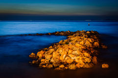 Magical Rocky Shoreline Sunset. Strange looking set of rocks nearby the shoreline during sunset with beautiful colors in Marmara sea of the country Turkey. Early Stock Images