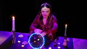 In the magical salon, the gypsy reads the future in a magical ball surrounded by glare. The average plan stock video