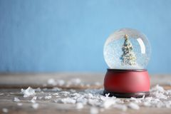 Magical snow globe with Christmas tree on table against color background. Space for text. Magical snow globe with Christmas tree on wooden table against color stock images