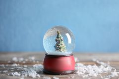 Magical snow globe with Christmas tree on wooden table. Against color background royalty free stock photography