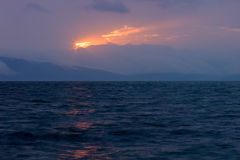 Magical sunlight in the dark clouds over the wavy lake of Sevan Royalty Free Stock Image