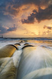Magical sunrise moment near the sea shore with cloudy sky.soft wave hitting the sandy beach. Beautiful and magical sunrise moment near the sea shore with cloudy Stock Photos