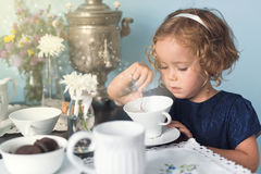Magical tea party with little curly girl Stock Images