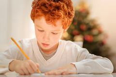 Concentrated kid writing letter to father christmas. Magical time of the year. Adorable redhead boy sitting at a table and focusing on a piece of paper while Stock Image