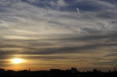 Gorgeous sunset strata cloudscape. Magical view of gorgeous sunset over cityscape stock photo