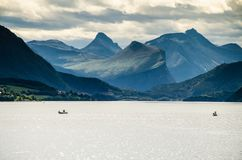 Magical view of two boats sailing on a Norwegian fjord with mountains behind and cloudy sky. royalty free stock photos