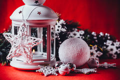 Magical white lantern is standing with white knit star on it and a fir tree branch and a snowball on a christmas red background. Royalty Free Stock Image