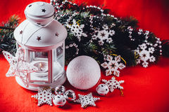 Magical white lantern is standing with white knit star on it and a fir tree branch and a snowball on a christmas red background. Stock Images