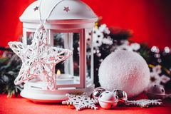 Magical white lantern is standing with white knit star on it and a fir tree branch and a snowball on a christmas red background. Royalty Free Stock Images