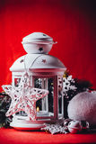 Magical white lantern is standing with white knit star on it and a fir tree branch and a snowball on a christmas red background. Stock Photo