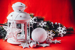 Magical white lantern is standing with white knit star on it and a fir tree branch and a snowball on a christmas red background. Stock Image