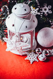 Magical white lantern is standing with white knit star on it and a fir tree branch and a snowball on a christmas red background. Royalty Free Stock Photos