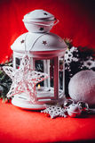 Magical white lantern is standing with white knit star on it and a fir tree branch and a snowball on a christmas red background. Stock Photography