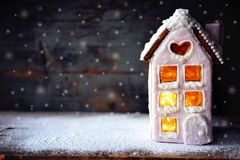 Magical winter christmas picture. Gingerbread house with snow. Magical winter christmas picture. Gingerbread house with pink icing with light glimming in the stock photos
