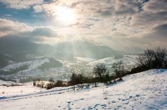 Magical winter countryside. Sun ray through the cloudy sky. snowy hill and leafless trees. village down in the valley royalty free stock photo