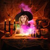 Magical Witch Reading Spell Book. A little girl is dressed up in a halloween witch costume with a glowing spell book of magic for an imagination or scary story Stock Photo