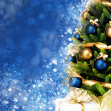Magically decorated Christmas Tree. With balls, ribbons and garlands on a blurred blue shiny, fairy and sparkling background Royalty Free Stock Photo