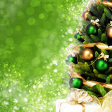 Magically decorated Christmas Tree with balls, ribbons and golden garlands on a blurred green shiny background Royalty Free Stock Photos