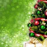 Magically decorated Christmas Tree with balls, ribbons and golden garlands on a blurred green shiny background. Magically decorated Christmas Tree with balls Stock Image