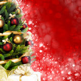 Magically decorated Fir Tree with balls, ribbons and garlands on a blurred Christmas-red shiny background Stock Image