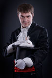 Magician. Man dressed as a magician pulling a rabbit from his hat Royalty Free Stock Photography