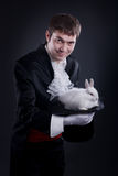 Magician. Man dressed as a magician pulling a rabbit from his hat royalty free stock photo