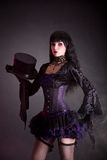 Magician assistant in purple and black gothic Halloween outfit Stock Photos