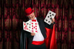 Magician with big cards. Mature magician on stage performing a magic trick with cards royalty free stock images