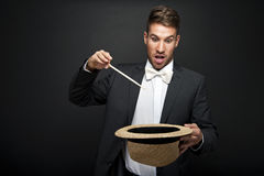A magician in a black suit holding an empty top hat Royalty Free Stock Photo