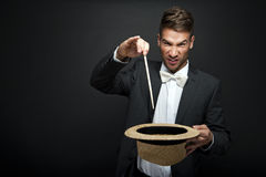 A magician in a black suit holding an empty top hat Royalty Free Stock Photography