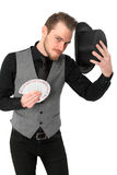 Magician with cards. Magician holding a card fan and top hat. Wearing a black shirt and vest. White background Stock Images