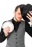 Magician with cards. Magician holding a card fan and top hat. Wearing a black shirt and vest. White background Stock Photo