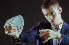 Magician with cards. Magician showing the cards for pose stock photos